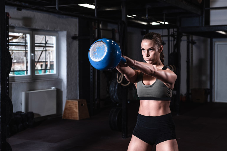 woman is performing Kettlebell Swing at gym