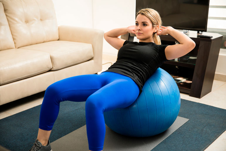 woman is performing crunches on stability ball