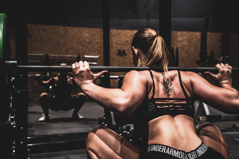woman is performing squats with barbell