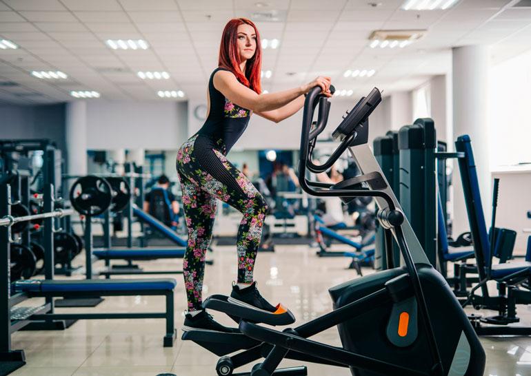 woman is posing on step machine