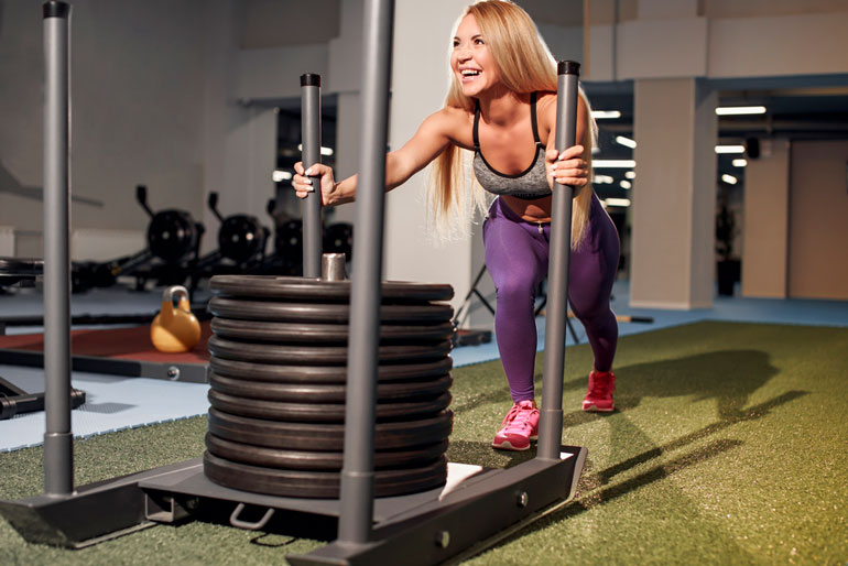 woman is pushing weight at gym