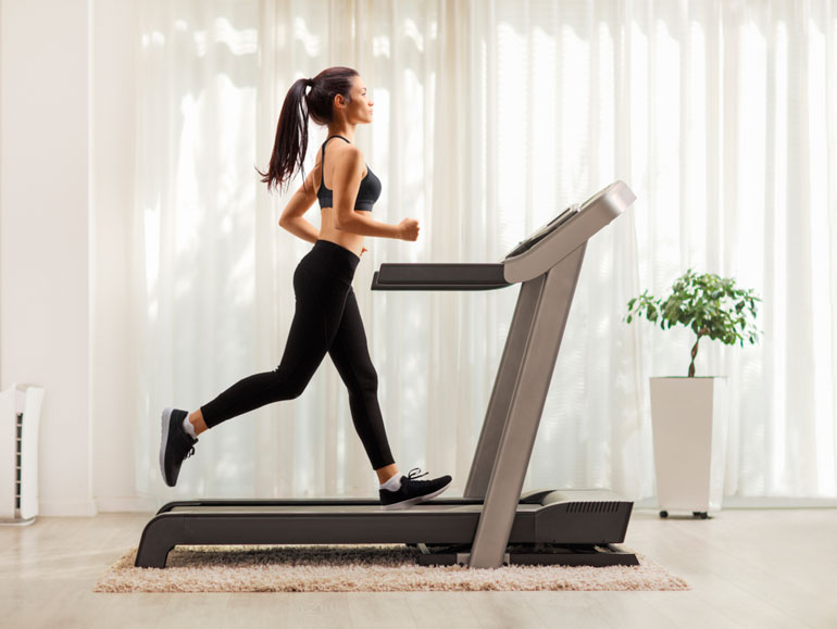 woman is running on treadmill at home