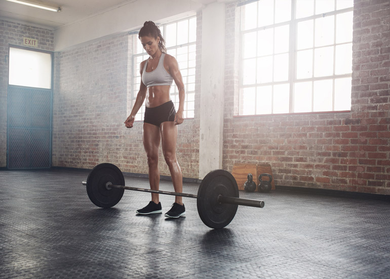 woman is standing behind barbell