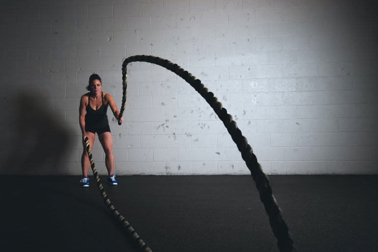 woman is swinging battle ropes