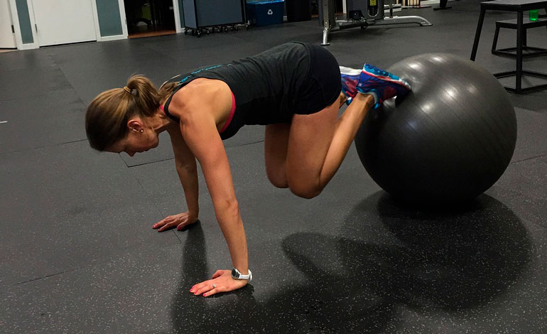 woman is training core with stability ball
