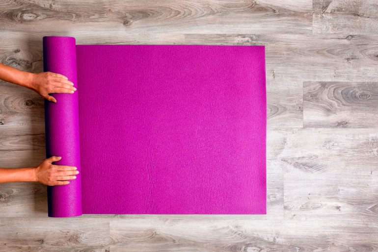 woman is unrolling a pink yoga mat