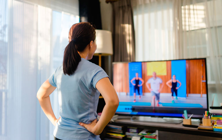 woman is watching people exercising on TV