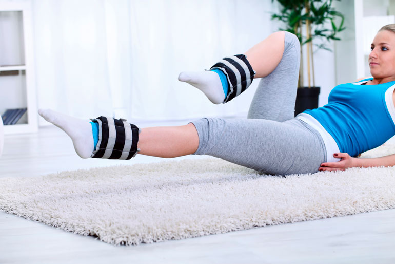 woman is working out with ankle weights