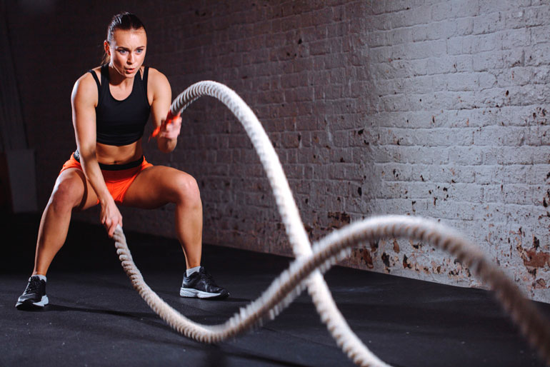 woman is working out with battle ropes