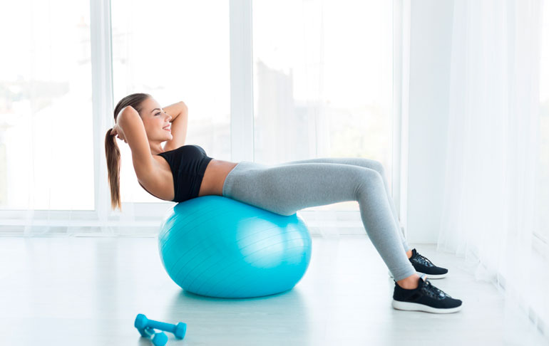 woman is working out with stability ball