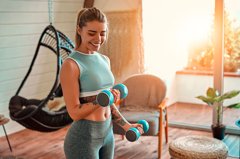 woman is working with blue dumbbells