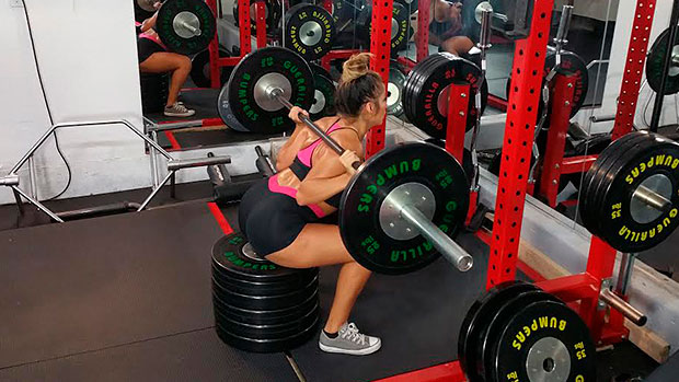 woman performing Box Squat with plates