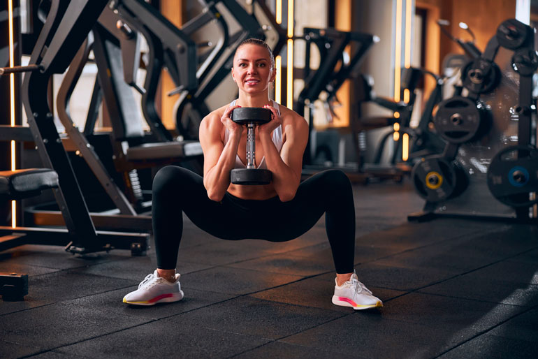 woman performing Goblet Squat with dumbbell