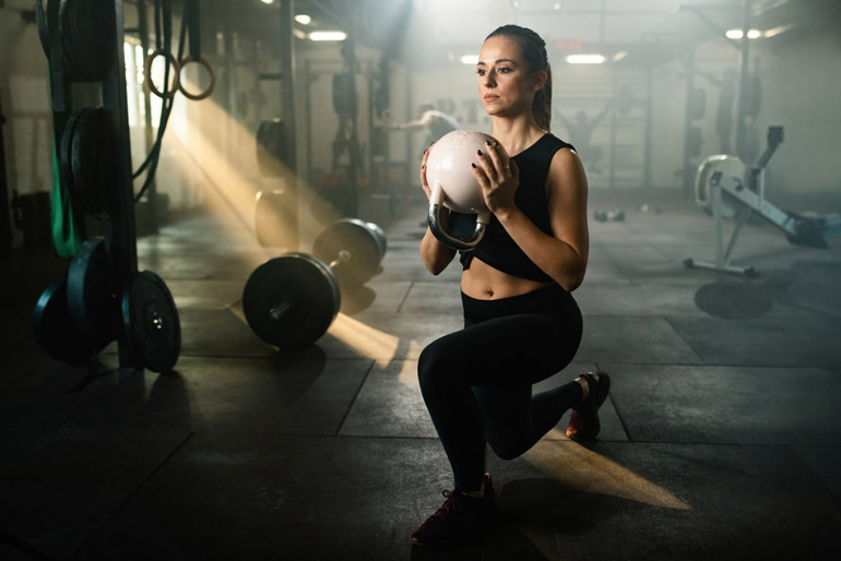 woman performing Split Squats with kettlebell