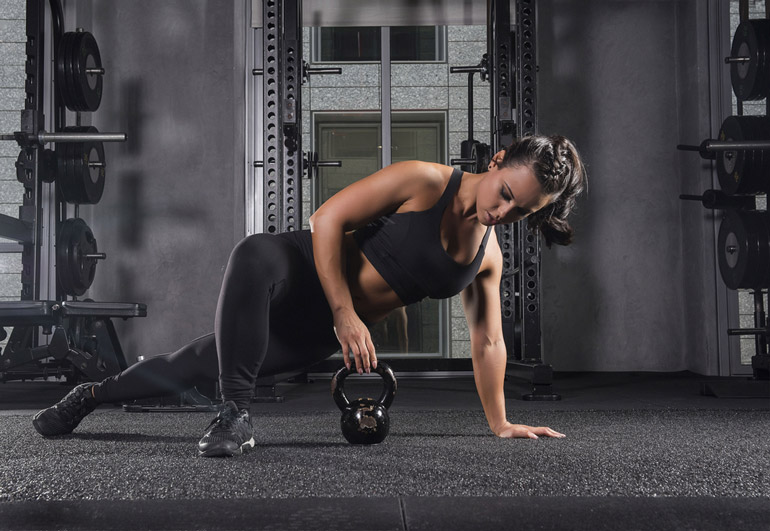 woman reaching the kettlebell on the floor