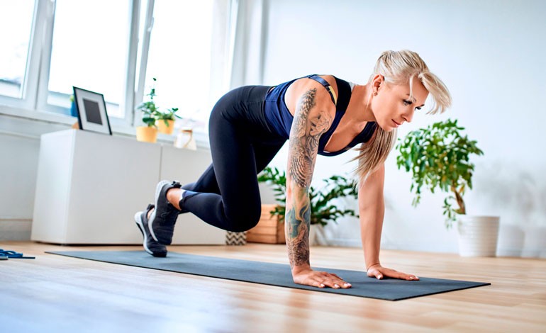 woman with tattoo is exercising on mat