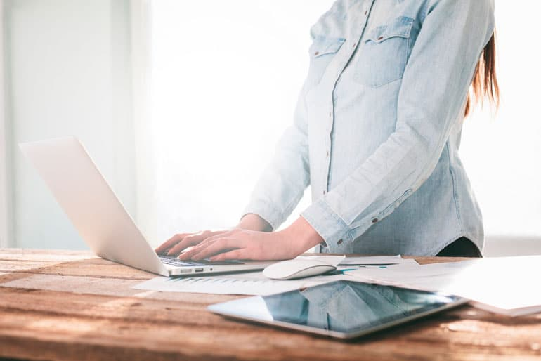 woman working with laptop on standing desk