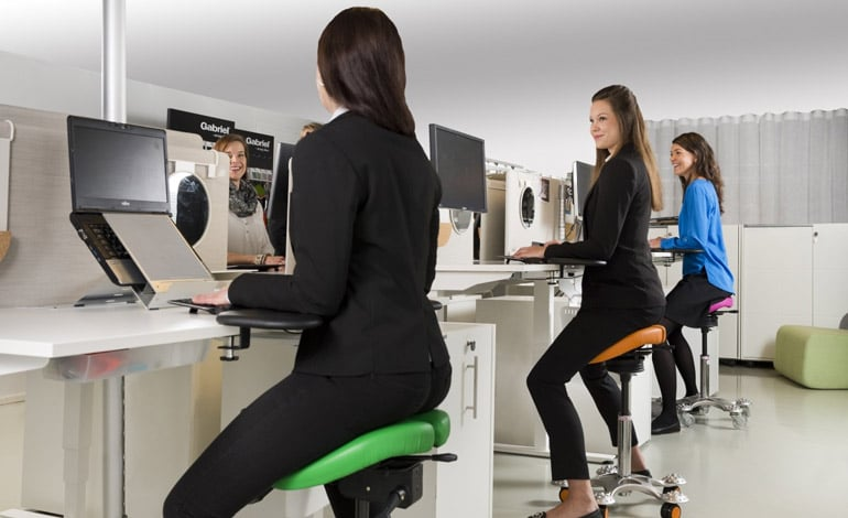 women sitting on saddle stools